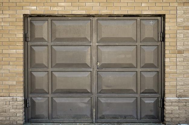 A textura de um portão de metal pintado de uma garagem de tijolos