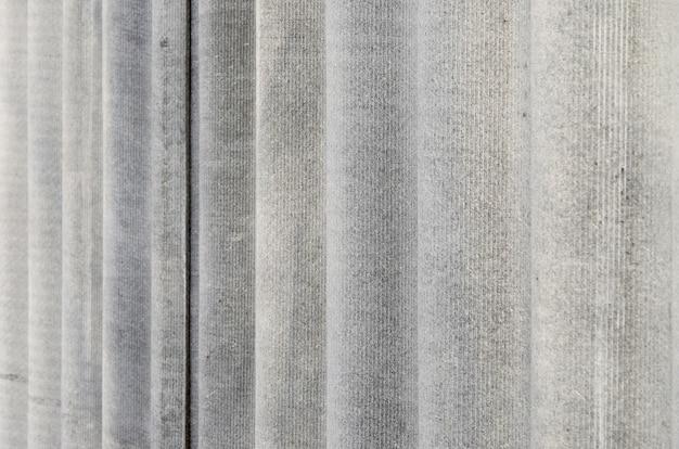 A textura de um velho telhado de casa de amianto em uma aldeia ou uma velha cerca pintada de arrepio de ardósia