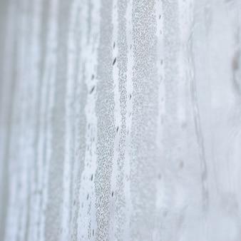 A textura de um vidro misted com muitas gotas e fluxos de condensação