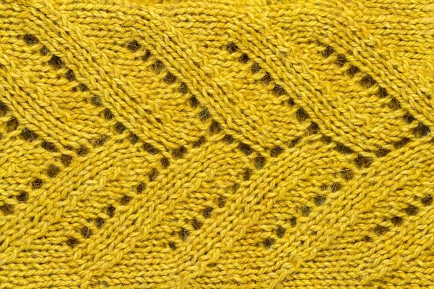 A textura de uma cor de fio de malha mostarda. roupas de malha e inverno