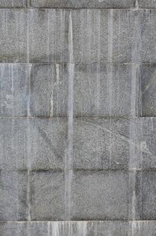 A textura de uma parede de grandes telhas de granito que são cobertas com estrias brancas quando expostas a umidade
