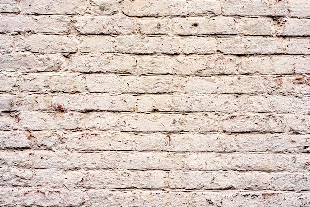 A textura de uma parede de tijolos com rachaduras e arranhões