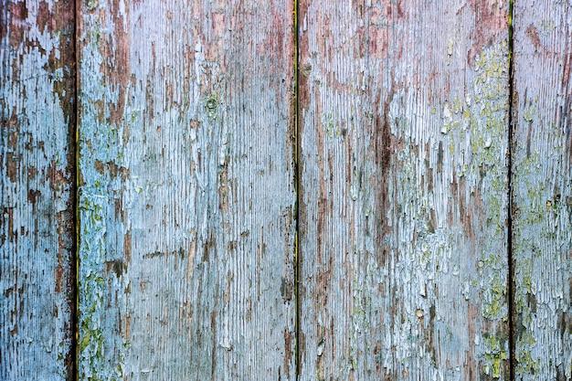 A textura de velhas tábuas de madeira rachadas com vestígios de tinta