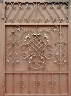 A textura do portão de metal bronze com um belo padrão floral de metal forjado