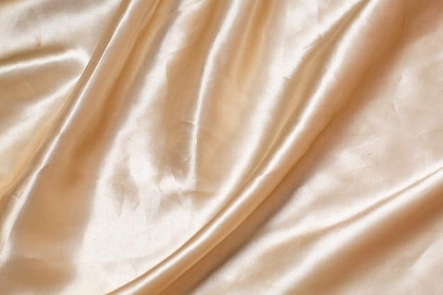 A textura do tecido de seda. tecido bege plissado.