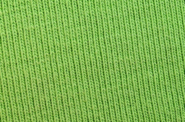 A textura do tecido é verde brilhante. material para fazer camisas e blusas