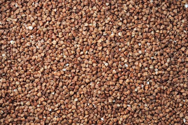A textura do trigo mourisco cru. marrom do trigo mourisco dos cereais do fundo natural. fechar-se.