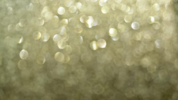 A textura dourada do papel glitter refletia a luz de fundo do bokeh