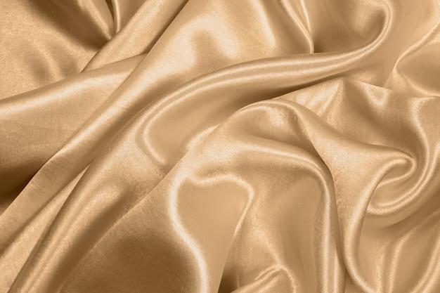A textura dourada elegante lisa bonita da seda ou do cetim pode usar-se como o fundo abstrato. cor de tecido