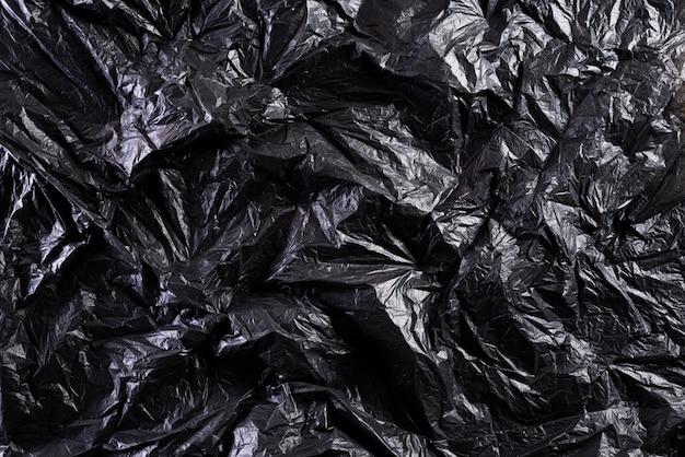 A textura e o fundo pretos do saco de plástico, reciclam e conceito do ambiente.