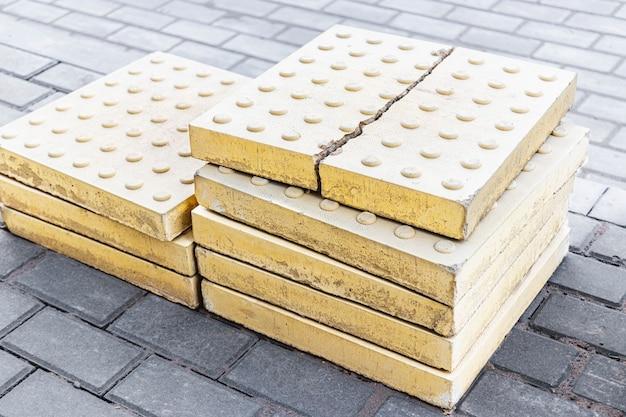 A textura tátil das lajes de pavimentação antes de serem colocadas na estrada. proteção de cegos em calçadas e passeios.