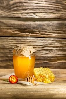 A tigela com mel na mesa de madeira. o banco de mel fica perto da colher de pau