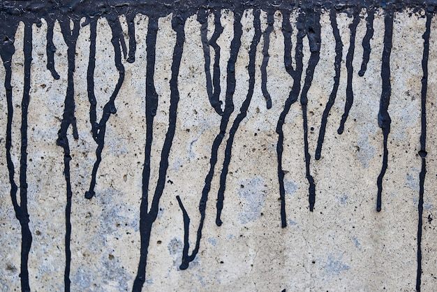 A tinta preta atual em uma parede desbotada áspera.