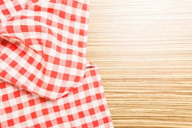 A toalha de mesa quadriculada na mesa de madeira