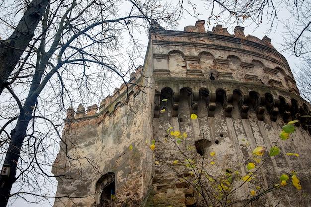 A torre da antiga fortaleza em ostrog, ucrânia, close-up. final de outono. folhas amarelas nos galhos das árvores
