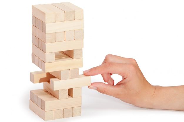 A torre de blocos de madeira e a mão do homem levam um quarteirão