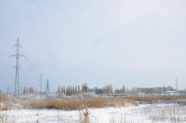 A torre de linha de energia está localizada em uma área pantanosa, coberta de neve