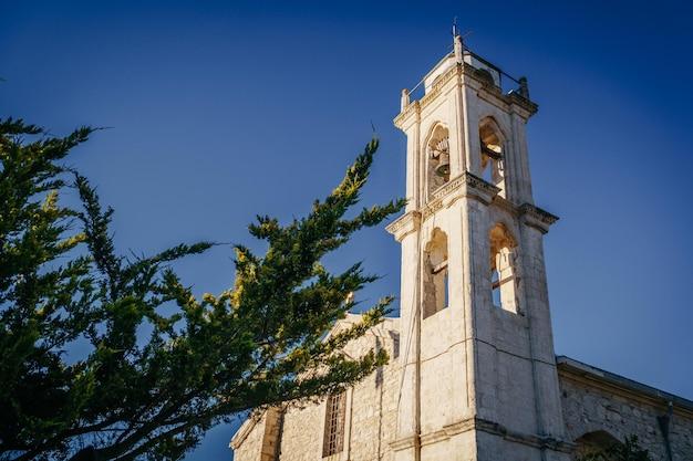 A torre do sino da velha igreja contra o céu azul