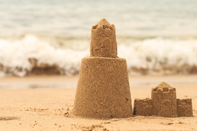 A torre persistente do castelo de areia é lavada pela água do mar.