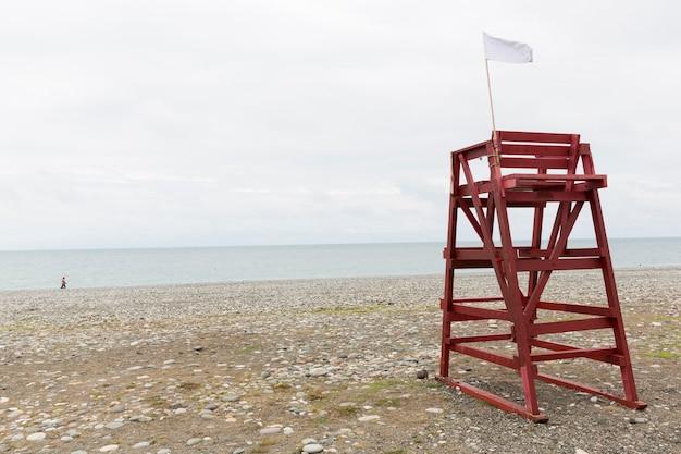 A torre vermelha do salva-vidas na praia de seixos da cidade turística está fora de temporada. sem pessoas, praia vazia. inverno, nuvens. montanhas ao fundo. foto de alta qualidade