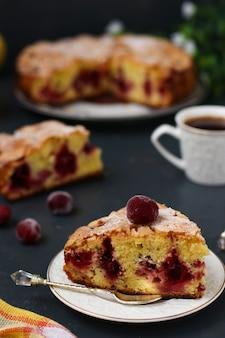 A torta de frutas vermelhas com cerejas está localizada em um prato sobre um fundo escuro. em primeiro plano está um pedaço de bolo e uma xícara de café