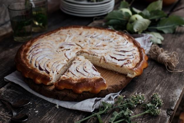 A torta de maçã foi cortada para o chá e colocada em uma mesa de madeira.