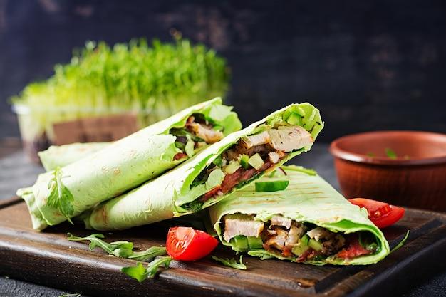 A tortilha fresca envolve com frango e legumes frescos na placa de madeira. burrito de galinha. conceito de comida saudável. cozinha mexicana.