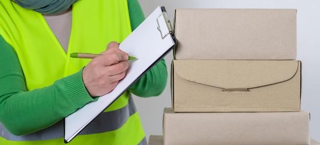 A trabalhadora está em um colete verde em pé perto de um monte de caixas de papel com pedido em branco, conceito de entrega.
