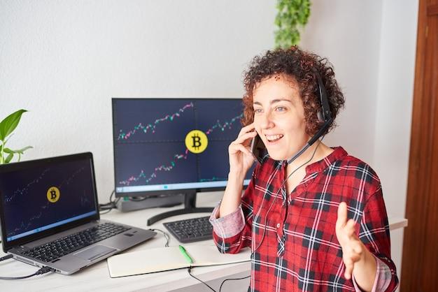 A trader trabalha com bitcoins em sua mesa enquanto fala ao telefone celular e usa um fone de ouvido