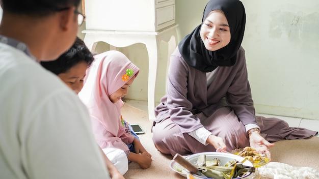 A tradição da família de eid al-fitr é comer ketupat opor ou acompanhamentos