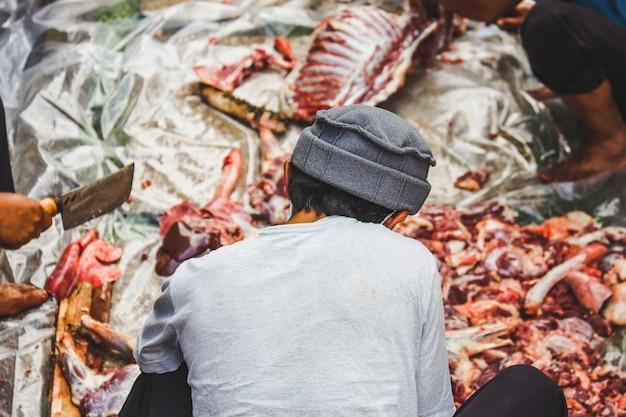 A tradição muçulmana da indonésia ajuda uns aos outros a preparar carne halal para abate para distribuir às pessoas