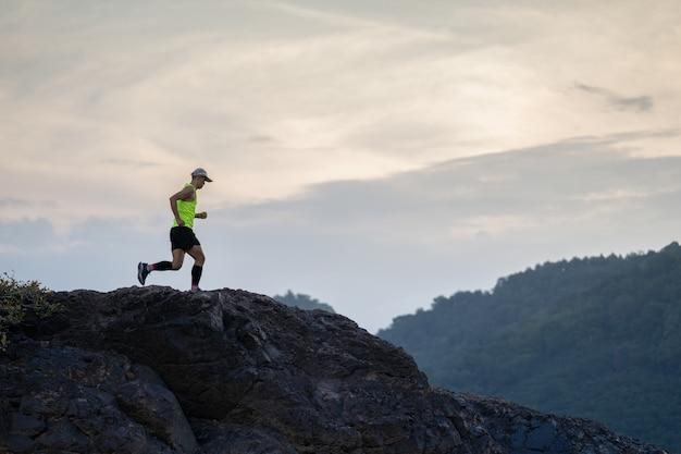 A trilha de atleta correndo na montanha de pedra