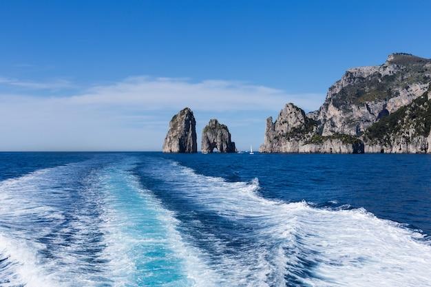 A trilha do navio de alta velocidade contra as rochas individuais no mar