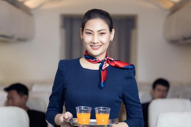 A tripulação de cabine serve água aos passageiros do avião. transporte de linha aérea e conceito de turismo.