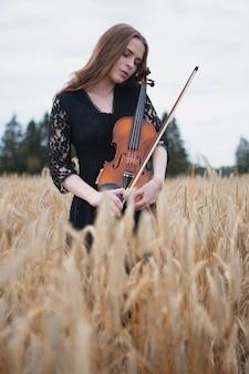 A triste violinista pressiona suavemente seu violino contra ela