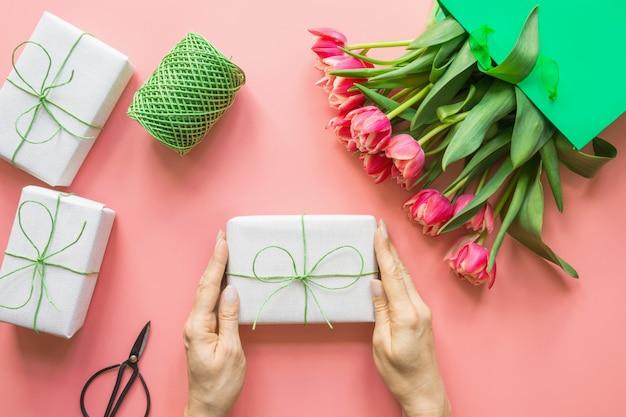 A tulipa vermelha fresca floresce no saco de papel verde no rosa. primavera. dia das mães.