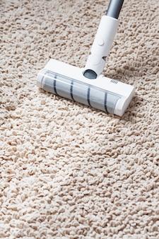 A turbo escova de um aspirador de pó sem fio limpa o carpete da casa em close-up. tecnologias modernas para limpeza.