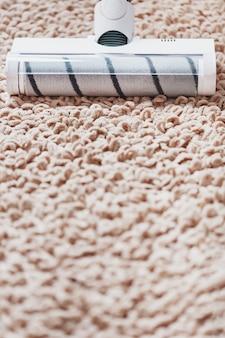 A turbo escova de um aspirador de pó sem fio limpa o carpete da casa em close