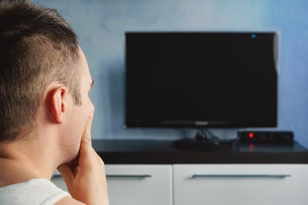 A tv não está funcionando. conceito de lazer, tecnologia, mídia de massa e pessoas - homem assistindo tv em casa de costas. tv não está funcionando
