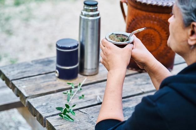 A uma mulher latina bebendo erva mate e se divertindo sentado a uma mesa de madeira no campo