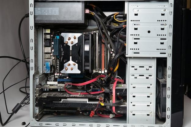 A unidade de sistema do computador é desmontada sem uma tampa. muitas peças antigas do computador. computador de dentro.