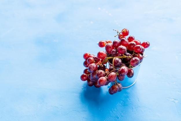 A uva vermelha com água deixa cair, close up, isolado no fundo azul uvas vermelhas frescas. tempo de colheita.