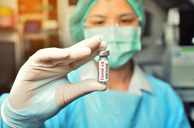 A vacina contra o coronavírus covid-19 em um cientista pesquisador com as mãos no ombro segurando uma seringa e um frasco com a vacina para o coronavírus. conceito de cuidados de saúde, médicos, de laboratório.