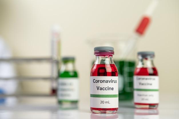 A vacina contra o covid-19 está em vermelho e verde em garrafas colocadas no chão.