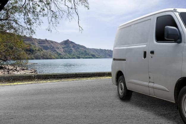 A van branca de entrega na estrada com lago e vale