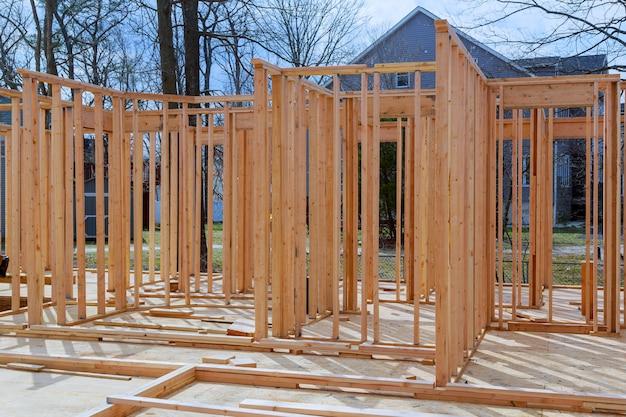 A vara nova do close-up construiu em casa sob a construção sob o quadro de madeira de quadro da estrutura do céu azul de casas de madeira em casa.
