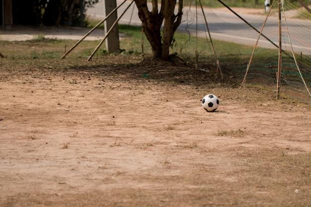 A velha bola de futebol na grama pior, campo de jogo de futebol pobre na zona rural