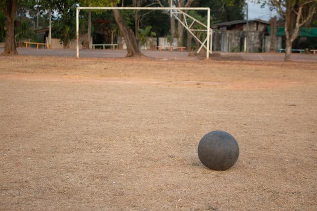A velha bola de futebol na grama pior, pobre campo de jogo de futebol na zona rural