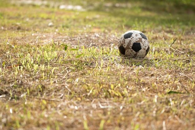 A velha bola de futebol na grama pior, poor campo de futebol no campo