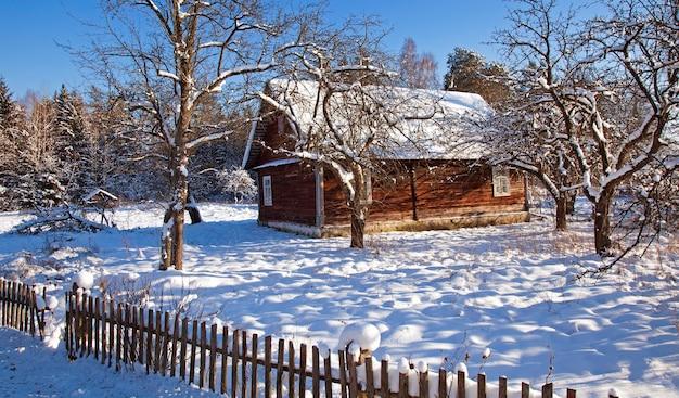 A velha casa de madeira coberta de neve no inverno